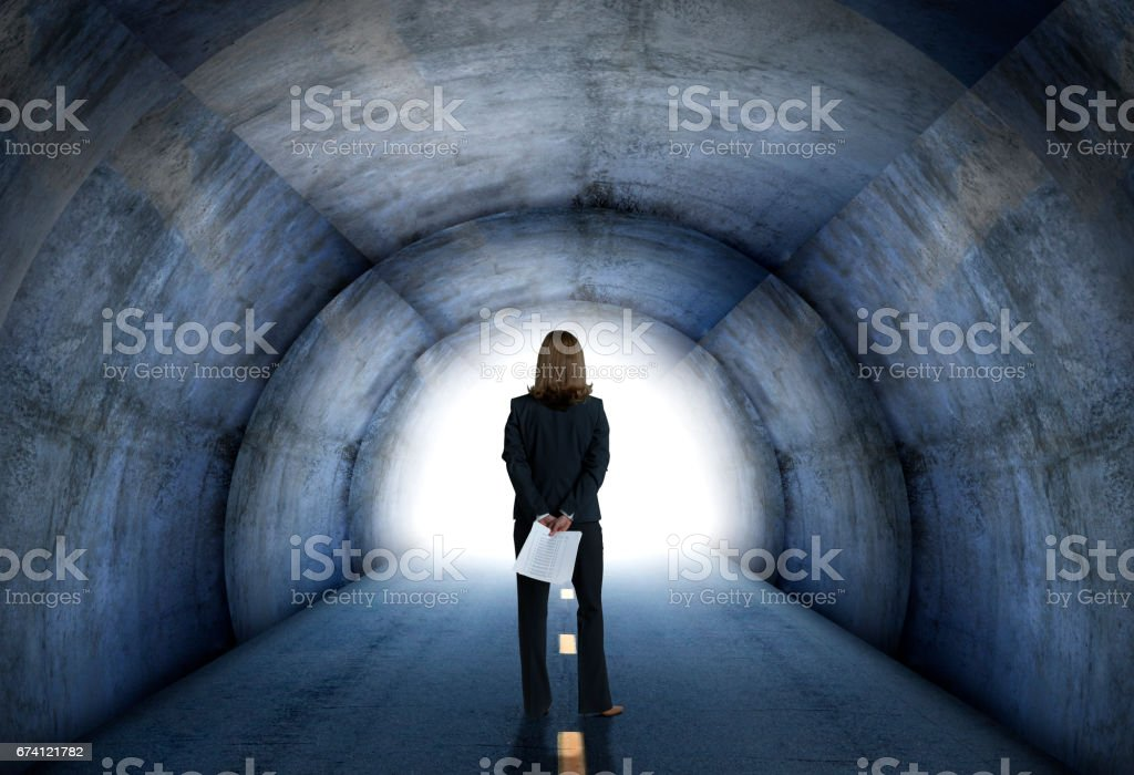 Businesswoman Looking Toward Light At End Of Tunnel stock photo