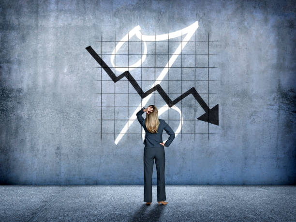 Businesswoman Looking Up At Falling Interest Rates stock photo