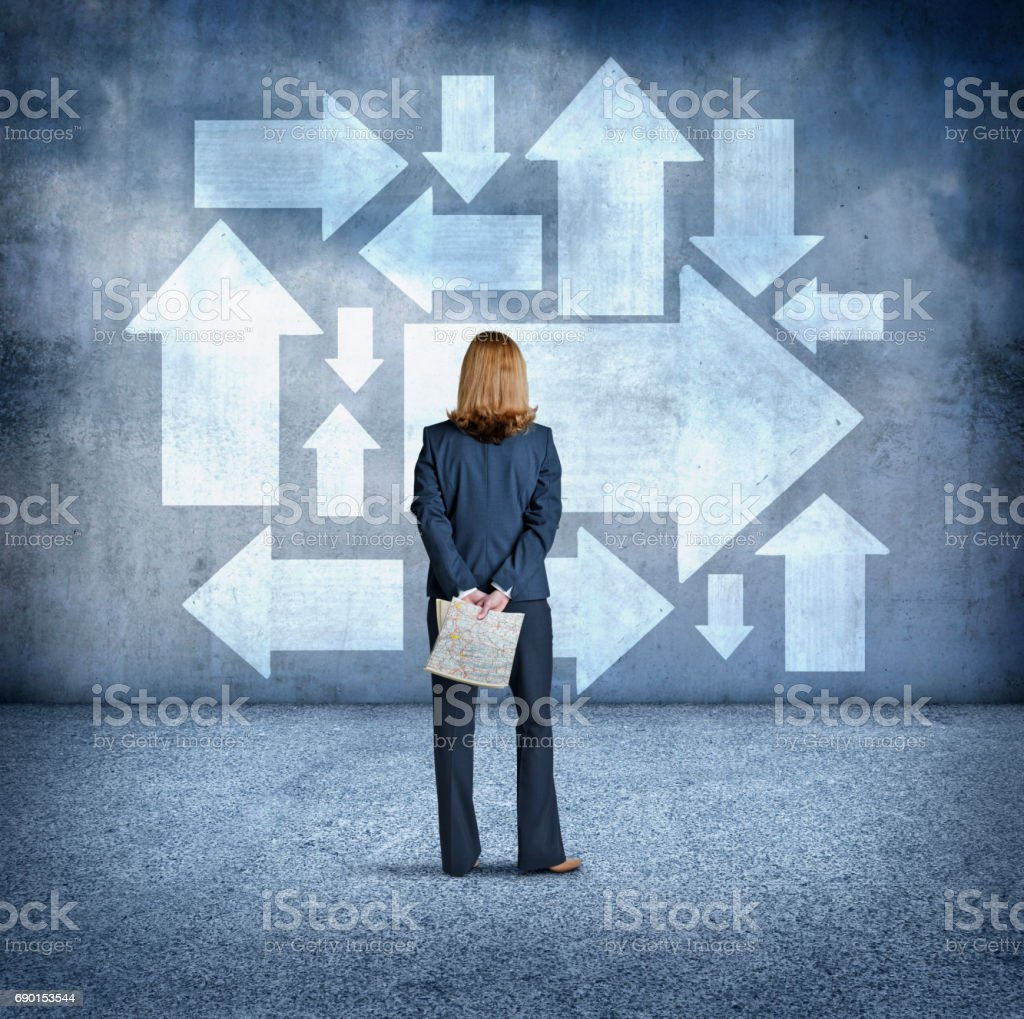 Businesswoman Looking Up At Large Arrows While Holding Road Map In Her Hands stock photo