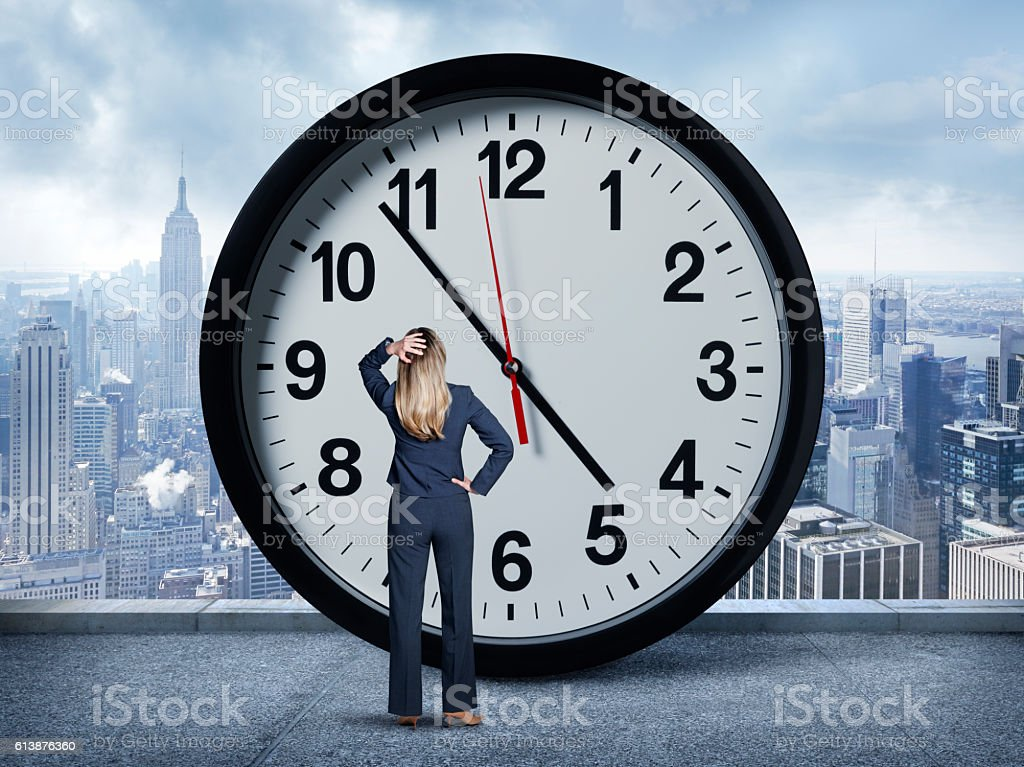 Businesswoman Looking Up At Large Clock stock photo