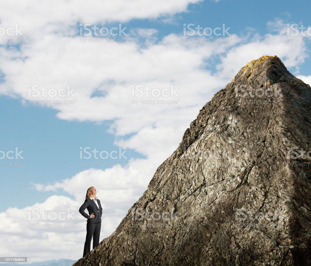 Businesswoman Looking Up At Mountain Peak stock photo