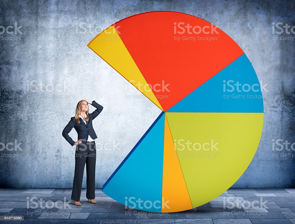 Businesswoman Looking Up At Pie Chart With Missing Piece stock photo