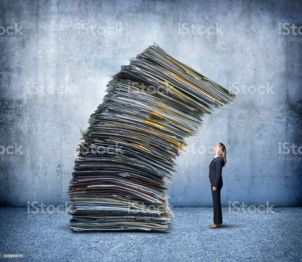 Businesswoman Looking Up At Stack Of Falling Paperwork stock photo