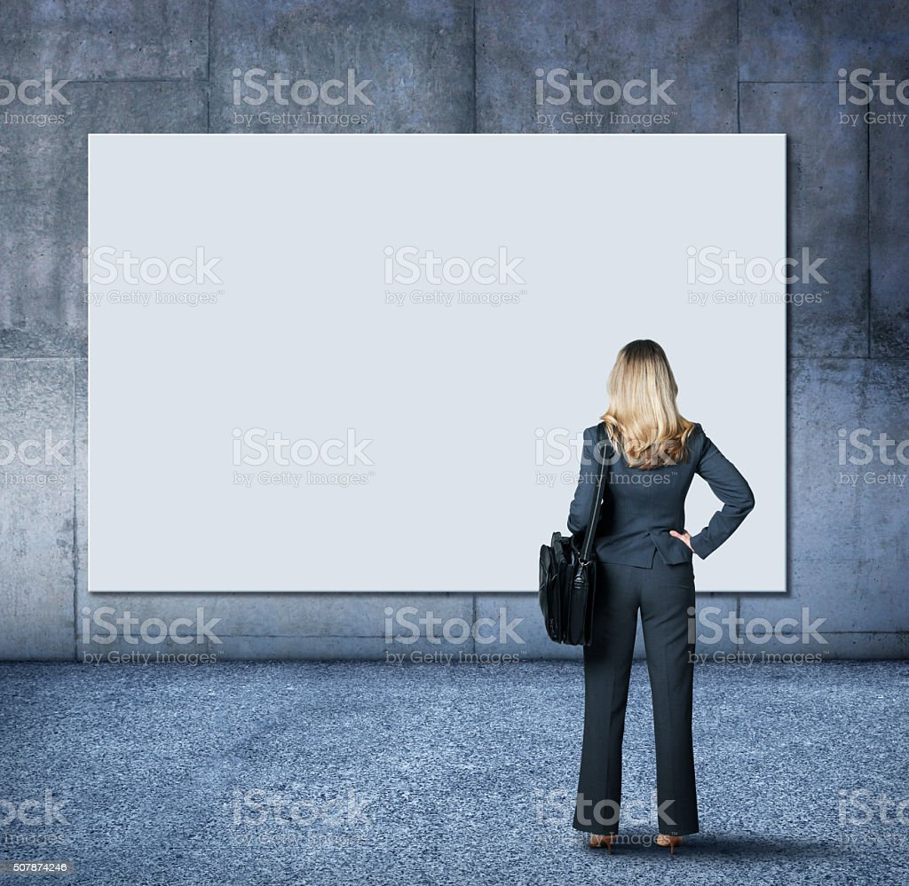 Businesswoman Looking Up Towards Blank Sign On A Wall stock photo