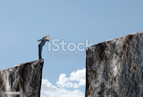 A businesswoman stands at the edge of a cliff and looks down at the large gap that prevents her from proceeding forward.