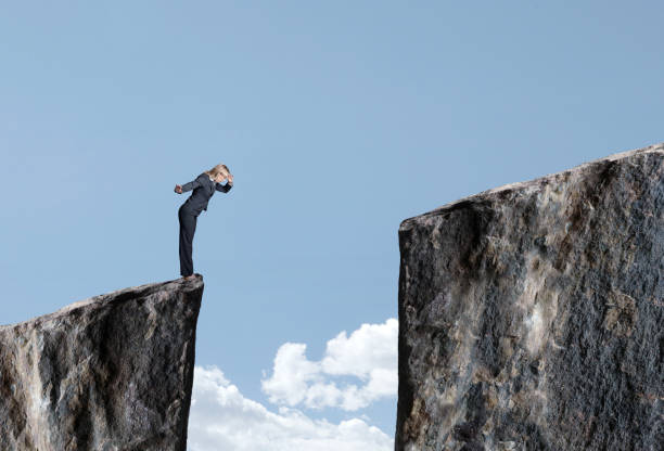 businesswoman looks down at large gap between two cliffs - gender stereotypes stock pictures, royalty-free photos & images