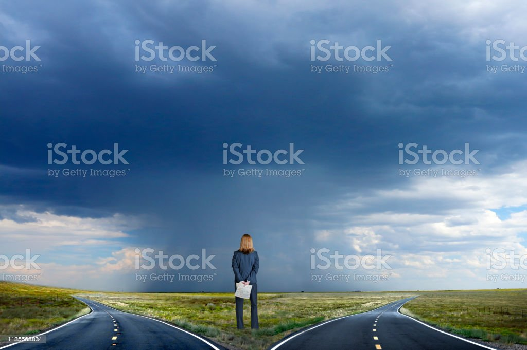 Businesswoman Looks Up At Blank Billboard As She Stand On Long Rural Road stock photo
