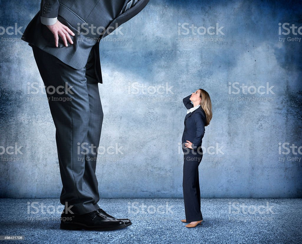 Businesswoman Looks Up Towards Much Larger Businessman stock photo