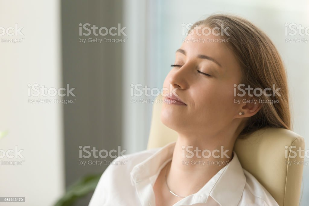 Businesswoman lying on back chair with closed eyes stock photo