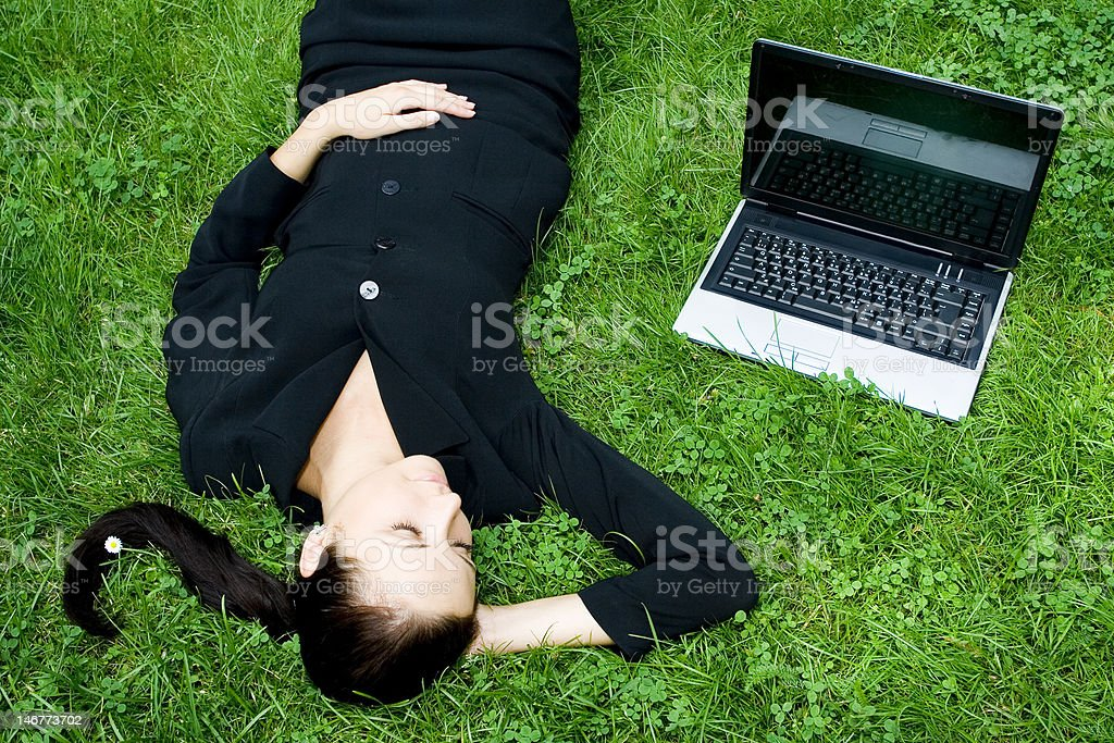 Businesswoman lying on grass with laptop royalty-free stock photo