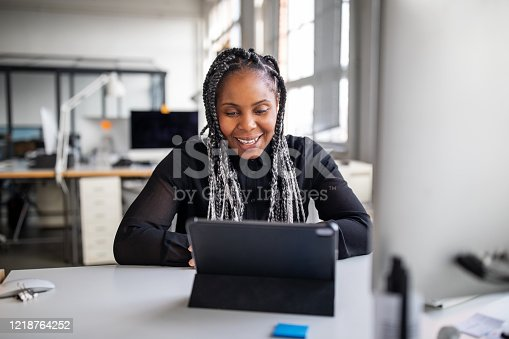 Smiling female executive sitting at her office desk making a video call with digital tablet. African american businesswoman working in office having a video conference.
