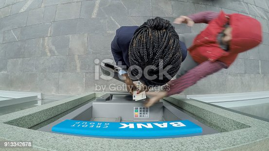 istock Businesswoman making cash withdrawal from ATM and being robbed in broad daylight 913342678