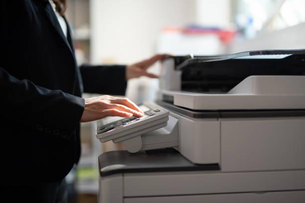 zakenvrouw het maken van kopieën met kopieermachine op kantoor - kopiëren stockfoto's en -beelden