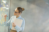 Young businesswoman in eyeglasses standing near the glass wall and writing her plans on adhesive notes at office