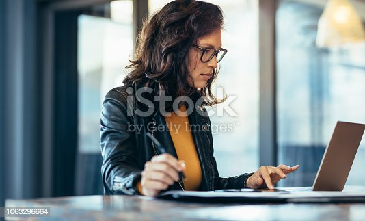 Businesswoman making notes looking at a laptop computer at office. Woman entrepreneur sitting at the table writing notes while working on laptop.