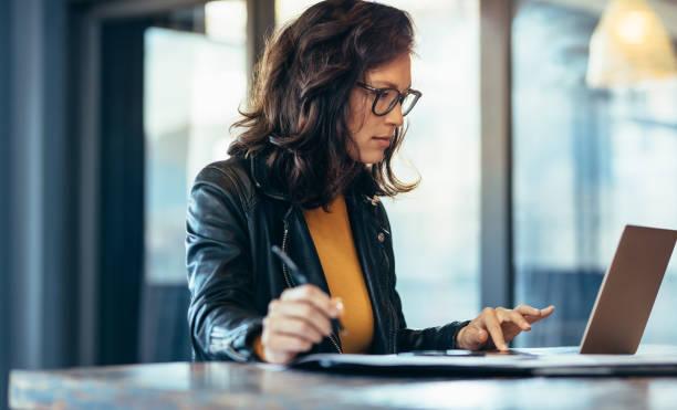 бизнесвумен делает заметки, глядя на ноутбук - писать стоковые фото и изображения
