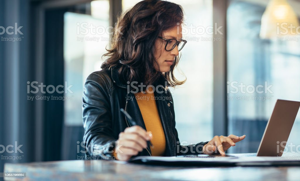 Businesswoman making notes looking at a laptop stock photo