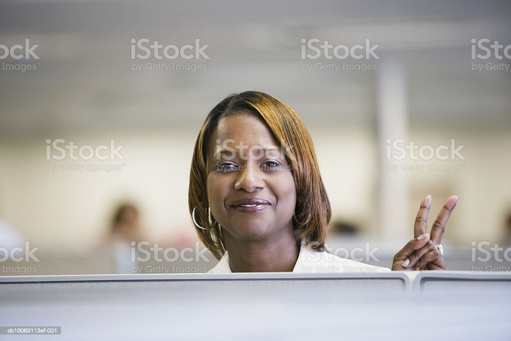 Businesswoman making V sign, smiling foto de stock royalty-free