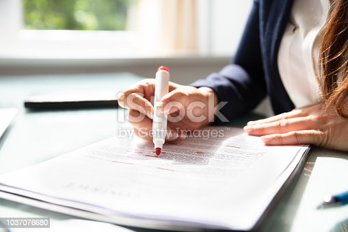 Businesswoman's Hand Marking Error In Contract Form With Marker
