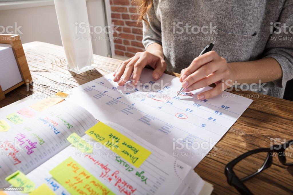 Businesswoman Marking Schedule On Calendar stock photo