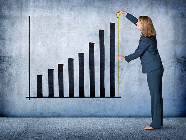 Businesswoman Measures Growth With Tape Measure stock photo