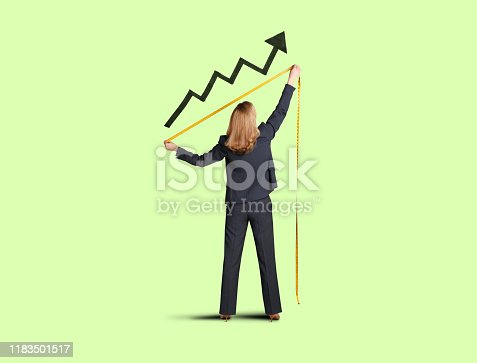 A businesswoman reaches up with a tape measure to measure her progress as indicated by a large black arrow on a chart isolated on a green background.