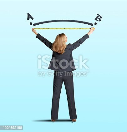 A businesswoman reaches up with a tape measure to measure the shortest distance between two points isolated on a greenish blue background.