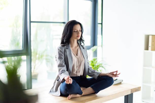 geschäftsfrau meditieren am arbeitsplatz - yoga fürs büro stock-fotos und bilder