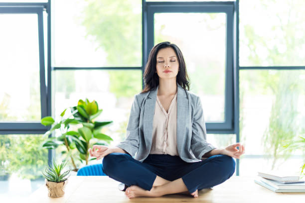 businesswoman meditating at workplace relaxed businesswoman with eyes closed meditating at workplace in office lotus position stock pictures, royalty-free photos & images