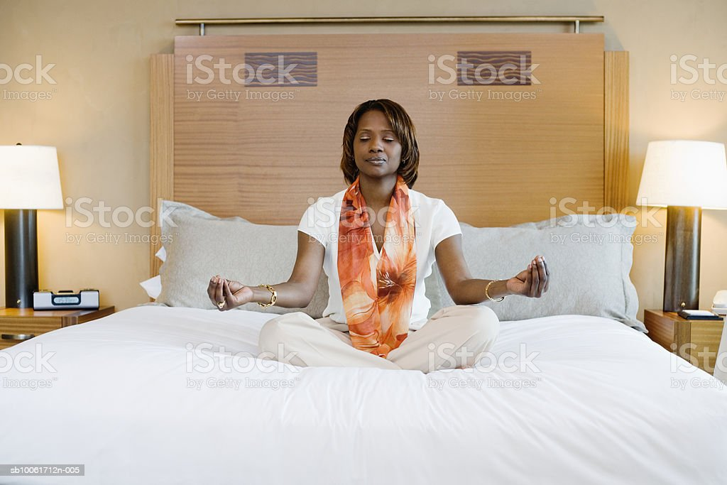 Businesswoman meditating in hotel room, eyes closed foto de stock libre de derechos