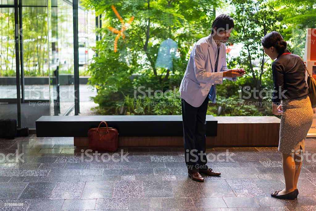 Businesswoman meeting businessman in office hall, Kyoto, Japan stock photo