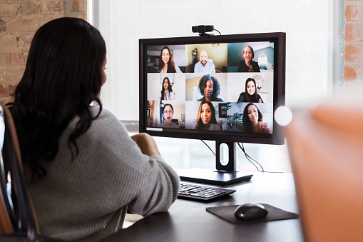 A group of diverse business colleagues participate in a virtual staff meeting during the COVID-19 pandemic. An African American businesswoman participates in the virtual event from her office.