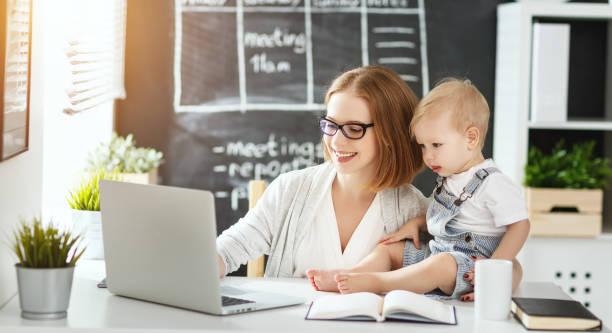 geschäftsfrau mutter frau mit kleinkind am computer arbeiten - letzter arbeitstag stock-fotos und bilder