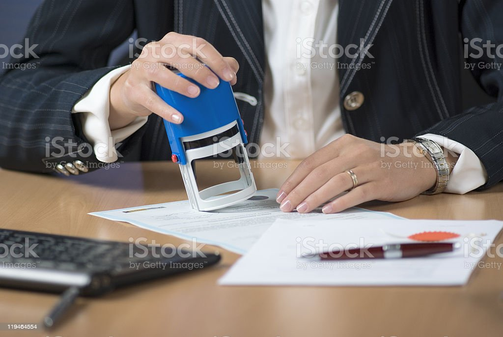 A businesswoman notarizing a document with a stamp stock photo