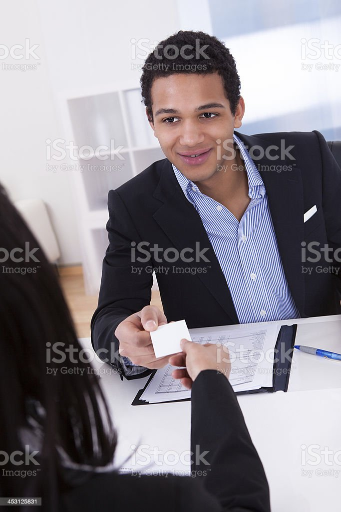 Businesswoman Offering Visiting Card To Man In Office royalty-free stock photo