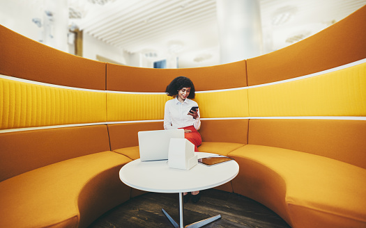 A wide-angle shot of a young elegant African-American businesswoman using her smartphone and gadgets while sitting on a round yellow sofa in office coworking area; woman entrepreneur with a cellphone
