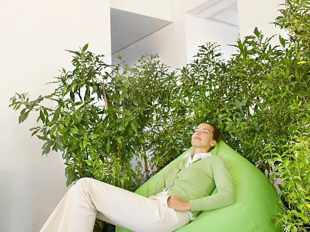 Femme allongé sur un siège réalisant une micro sieste pour réduire le stress au travail