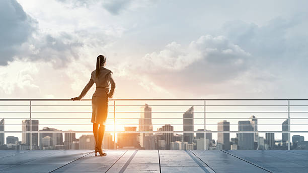 Businesswoman on building roof . Mixed media stock photo