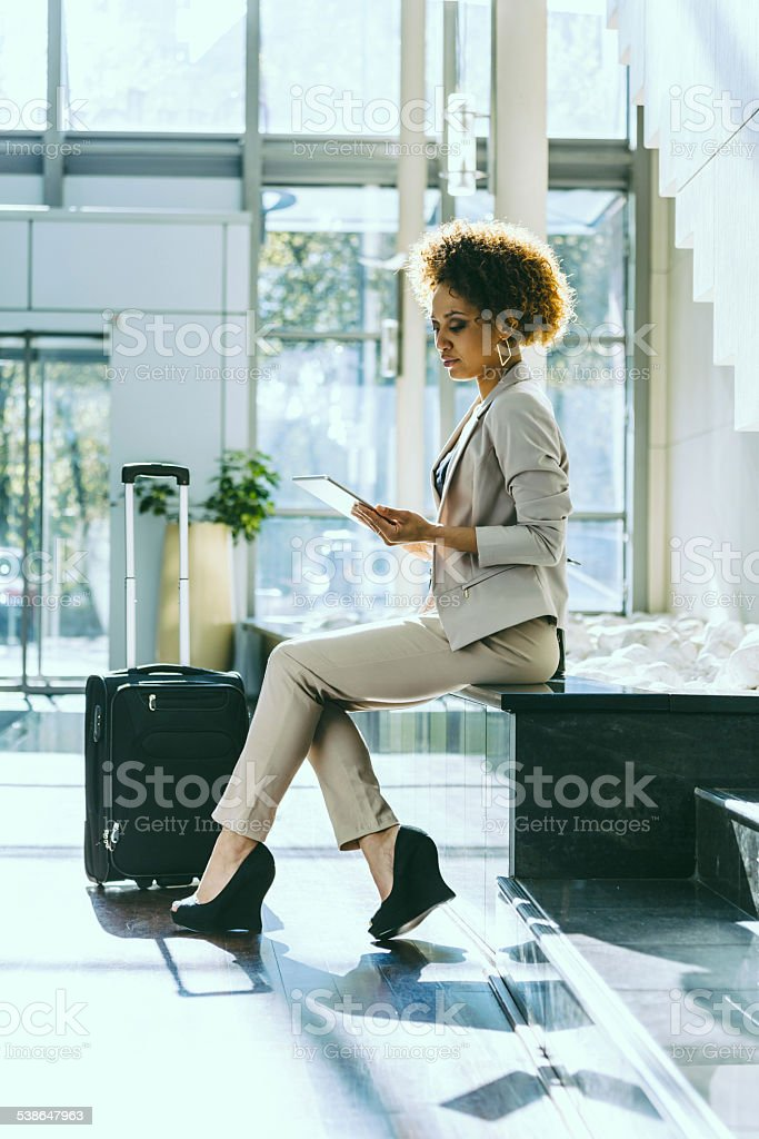 Businesswoman on business travel in hotel using tablet Afro american businesswoman sitting in a hotel hall and using a digital tablet, suitcase next to her.  2015 Stock Photo