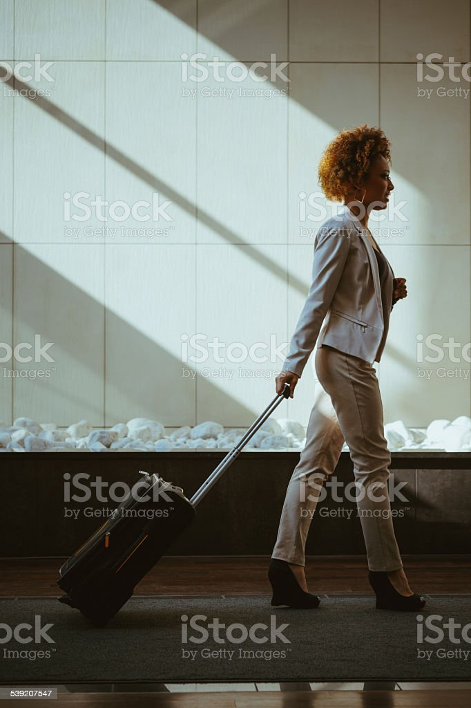 Businesswoman on business travel Side view of businesswoman walking on the hotel hall and carrying suitcases.  2015 Stock Photo