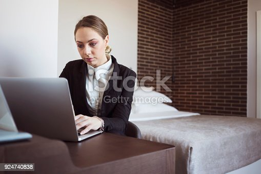 istock Businesswoman on business trip working in hotel room 924740838