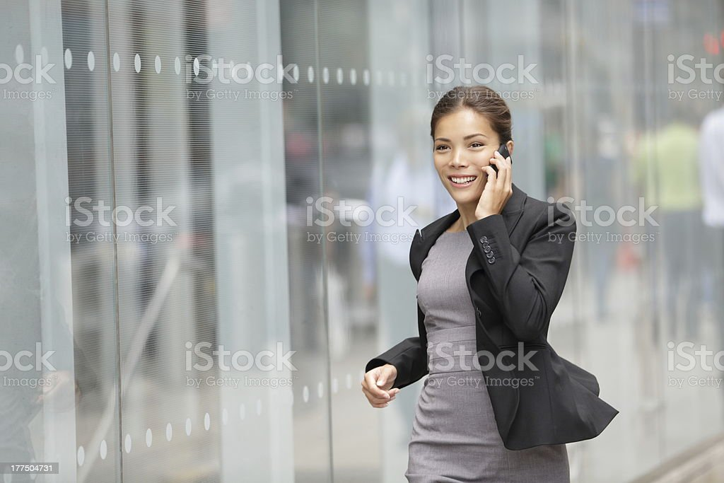 Businesswoman on cellphone running stock photo