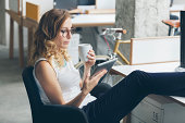 Young businesswoman drinking coffee and reading news from digital tablet with feet up.