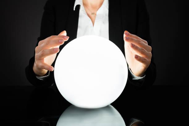 femme d'affaires sur la boule de cristal - boule de cristal photos et images de collection