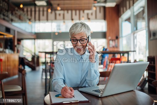 A happy businesswoman talking on the phone beside her laptop and taking notes.