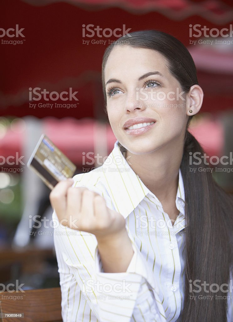 Businesswoman on outdoor patio holding credit card 免版稅 stock photo