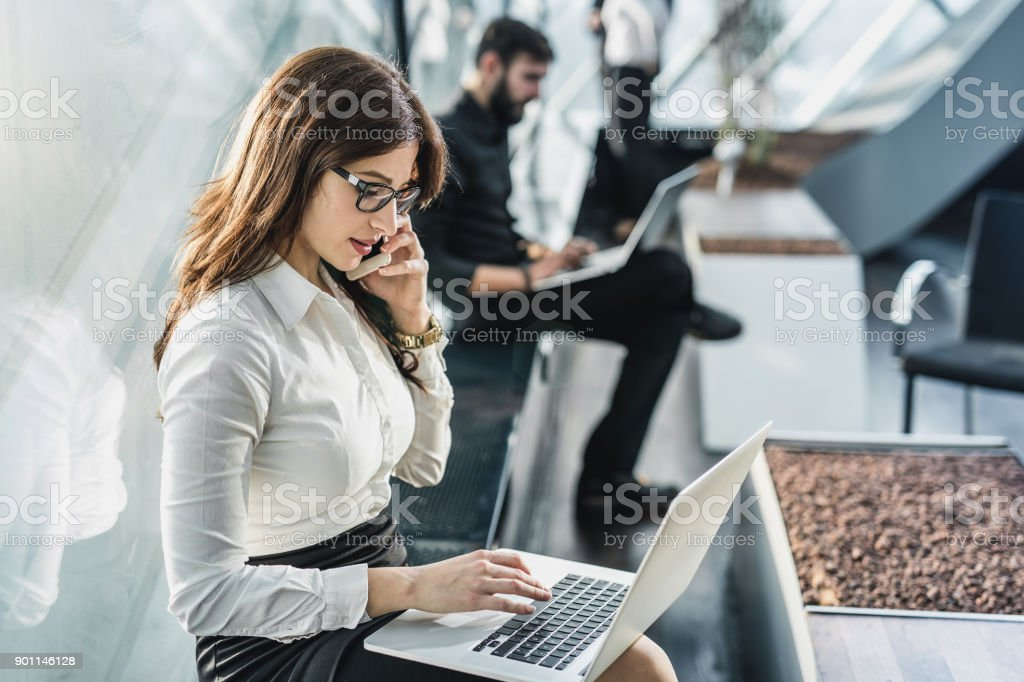 Geschäftsfrau auf Handy und Laptop verwenden – Foto