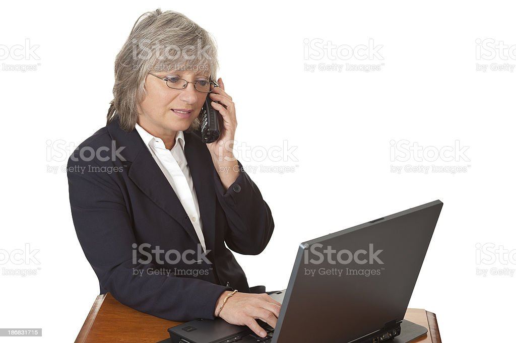 Businesswoman on phone and working with laptop computer royalty-free stock photo