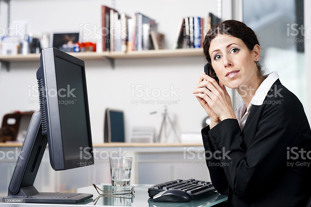 Businesswoman on phone looking at the camera stock photo