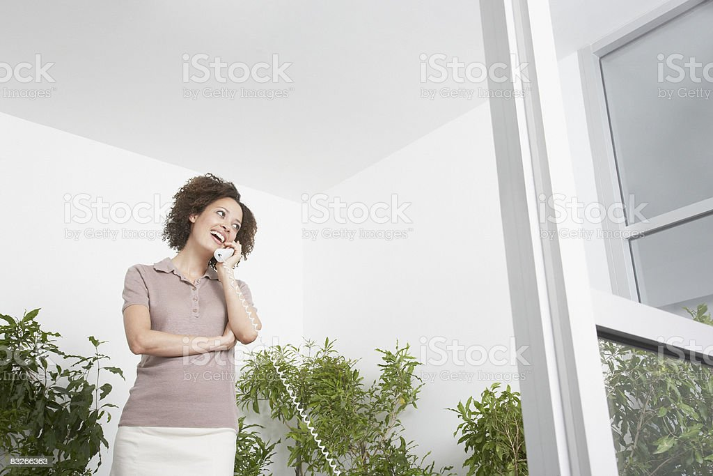 Businesswoman on phone surrounded by trees royalty free stockfoto